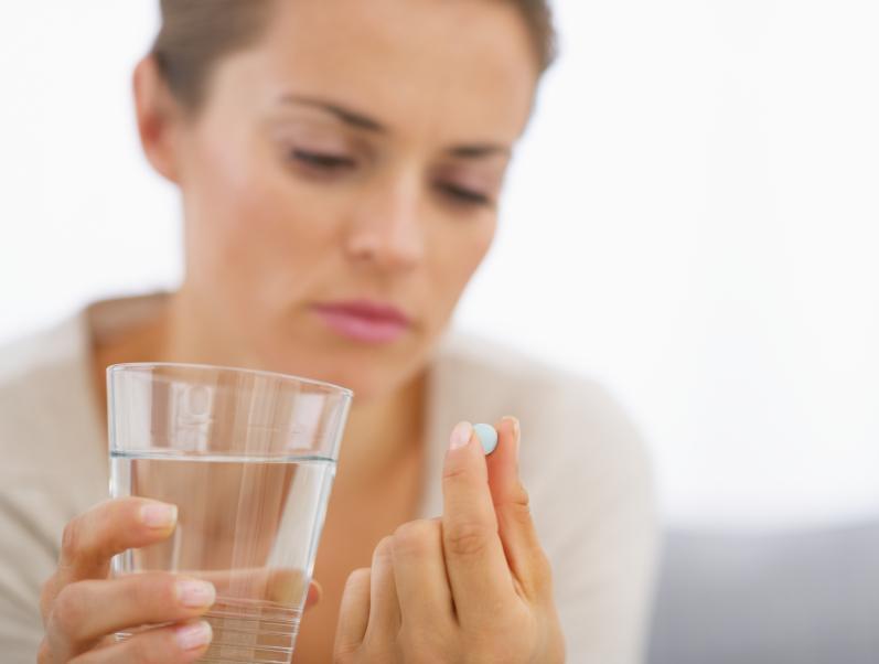 Mujer tomando pastilla de dinitrato de isosorbida