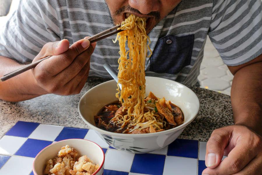 persona comiendo noodles
